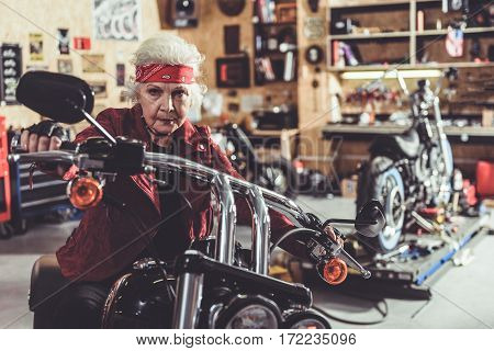 Calm retiree sitting on big motorcycle in wide cozy garage. Different instruments for vehicles are on shelves and posters hanging on the wall