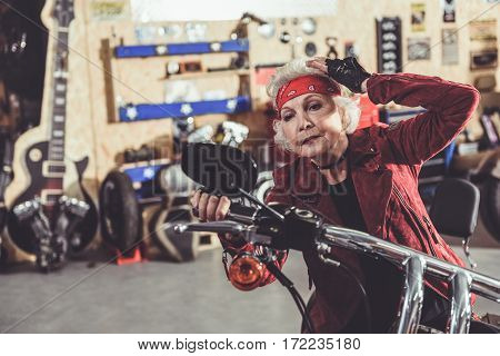 Concentrated female pensioner looking at mirror of motorcycle while sitting on it in cozy garage