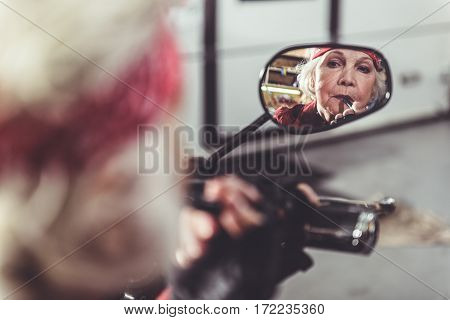 Cool female retiree making her lips up while watching at mirror of motorcycle in mechanic shop