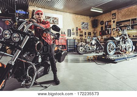 Pleased female pensioner locating on bike in wide garage with various vehicle appliances in it