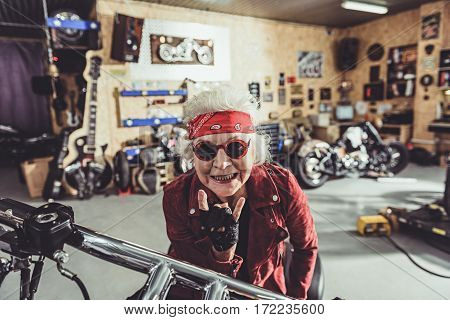 Cheerful old woman showing sign cool by gesture while sitting on motorcycle in mechanic shop