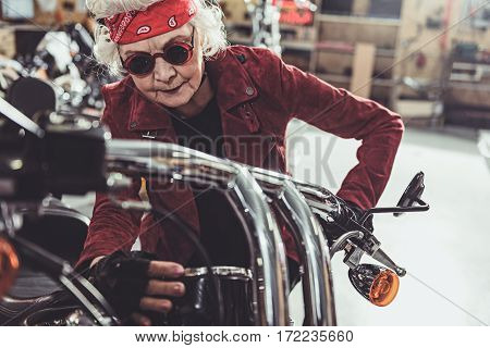 Serene pensioner looking at distance meter of bike while standing near it in garage