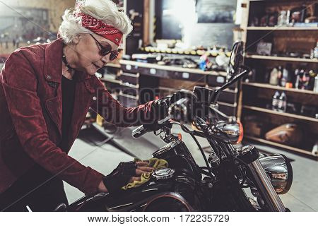 Smiling grandmother burnishing her bike while situating opposite shelves with instruments in comfortable garage