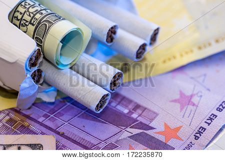 Cigarettes In A Pack On The Dollar And Euro Banknotes.