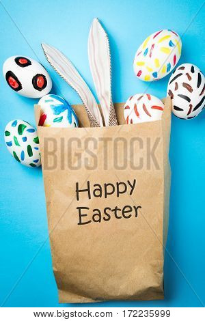 Easter bunny in a paper bag. Blue background. Easter ideas. Easter eggs. Space for text. Black lettering happy easter.