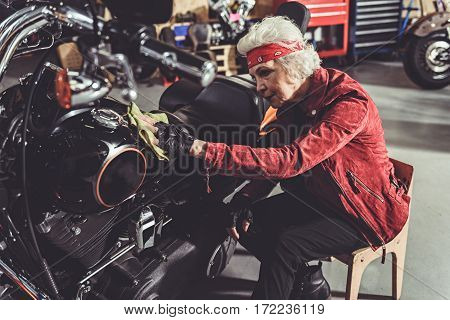 Calm old woman burnishing bike while sitting near it on little chair in garage