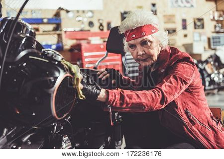 Cool pensioner cleaning motorcycle while situating near it on small seat in mechanic shop
