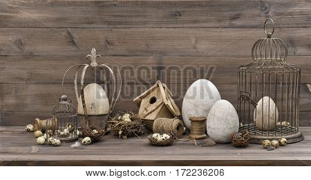 Vintage Easter decoration with eggs nest and birdcage. Nostalgic still life on wooden background