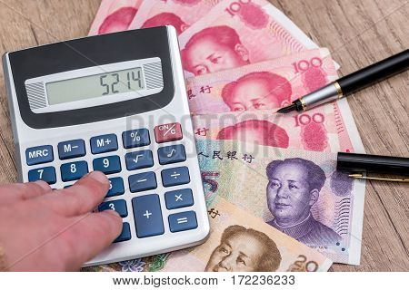 Chinese Yuan Banknote Money With Calculator On Desk.