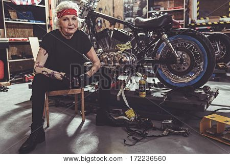 Smiling female pensioner sitting on little chair near her bike in garage