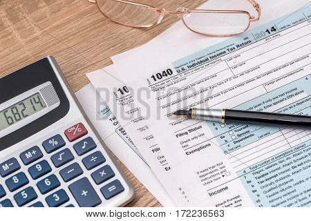 2017 year tax form 1040 with calculator and pen.