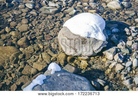 Stones and snow in the winter in the river ice