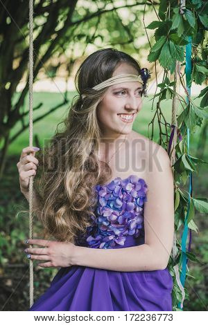 girl sits on a swing in the summer garden