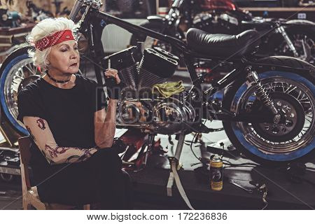 Serious female pensioner smoking while sitting next to bike in mechanic shop