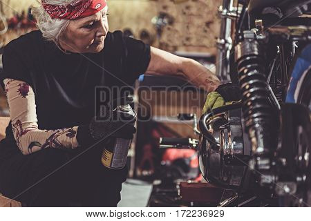 Calm grandmother cleaning bike while holding aerosol can in her hand in mechanic shop