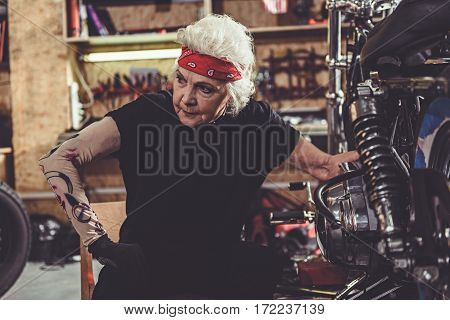 Serene female retiree sitting next to motorcycle while leaning against it in mechanic shop