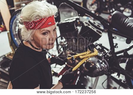Serene old woman making machine maintenance with wrench assembly in cozy mechanic shop