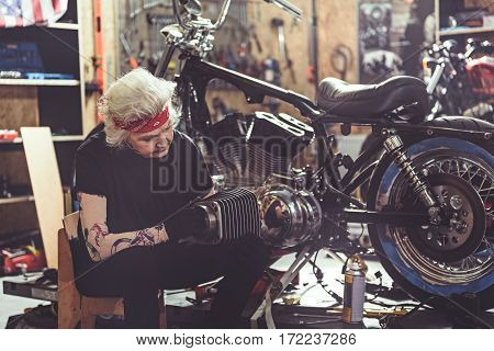 Thoughtful female retiree repairing motorcycle while sitting next to it in comfortable garage