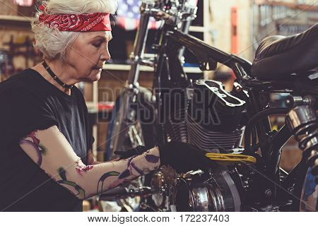 Calm female pensioner making machine maintenance with wrench assembly in comfortable mechanic shop