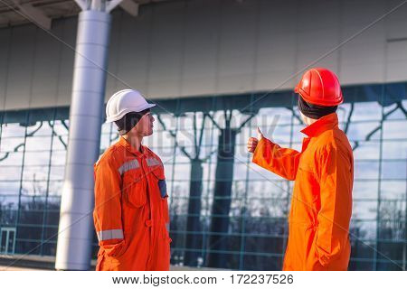 team of young engineers discussing a construction project and showing thumbs up. The wear overalls and safety helmets. Business modern background