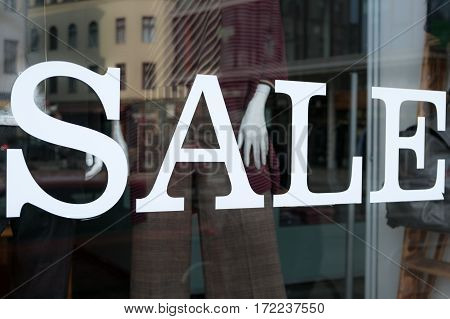 sale text on shopping window at fashion store