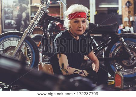 Serene old woman sitting next to motorcycle near instruments in mechanic shop