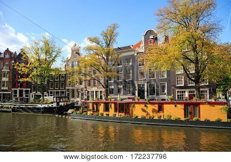Residential houses and Houseboats along the Prinsengracht canal  in autumn. Amsterdam, Netherlands