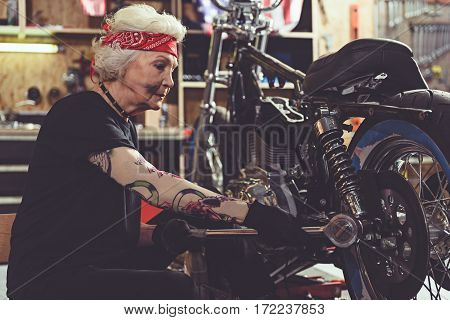 Calm grandmother repairing wheel of motorcycle with ratchet wrench in mechanic shop