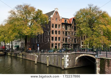 AMSTERDAM/ THE NETHERLANDS - OCTOBER 22, 2014. Old apartment house on the intersection of two canals: Prinsengracht and Brouwersgracht.