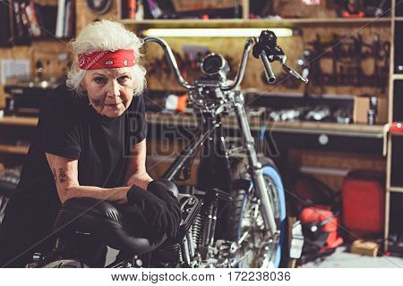 Serene fatigued old woman leaning on motorcycle in mechanic shop