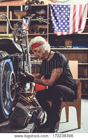 Pensive old woman doing motorcycle maintenance while locating next to it on chair in mechanic shop
