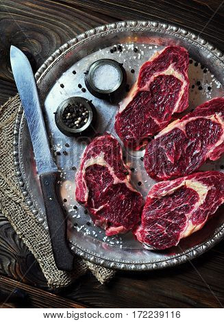 Raw fresh ribeye steak on the old serving tray.