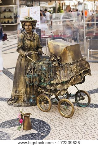 LISBON, PORTUGAL - September 26, 2016: A street performer plays a living statue in the Rua Augusta street in downtown Lisbon Portugal