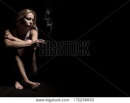 young woman sitting in dark smoking cigarette, image with copyspace