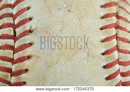 Macro image of the laced seams of a weathered and beaten old baseball. Sports background. Copy space