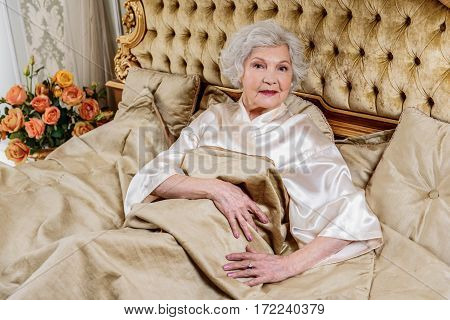 Elegant old woman is lying on classy bed and smiling