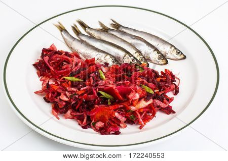 Sprats and vegetable salad on plate. Studio Photo