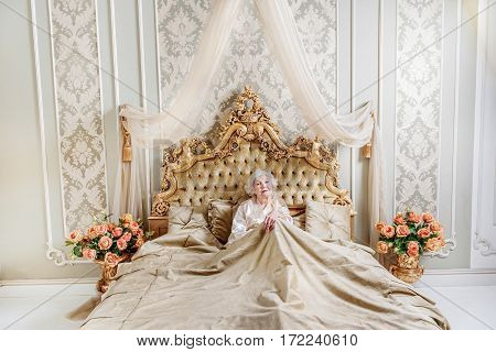 I am so lonely. Sad rich old woman is sitting on classic bed at home