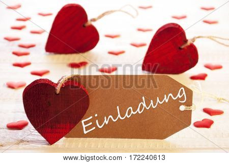 Label With German Text Einladung Means Invitation. Many Red Heart. Wooden Rustic Or Vintage Background.