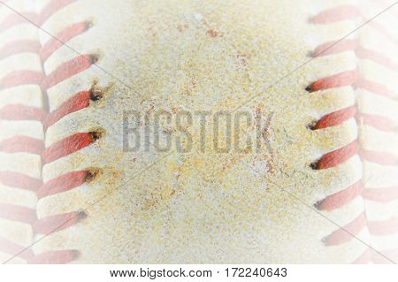 Macro image of the laced seams of a weathered and beaten old baseball. Sports background. White vignette added. Copy space
