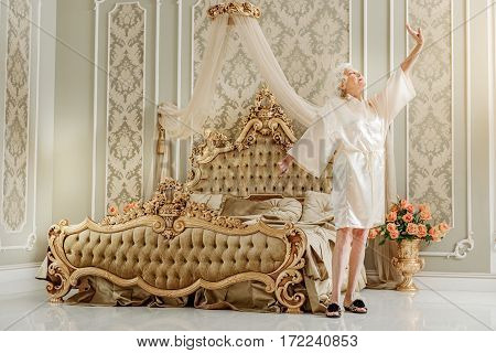 Good morning. Serene old rich woman is standing in bedroom and stretching arms after wake-up