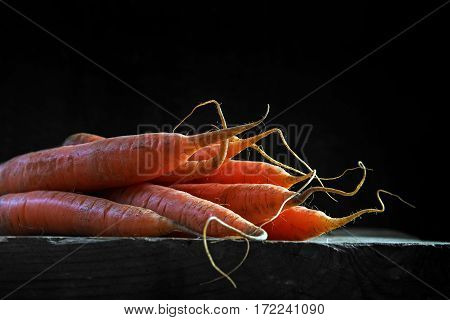 Carrots on a rustic wooden table against a dark background with copy space backlit closeup with selected focus an narrow depth of field