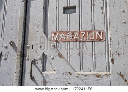 old wooden door with warehouse (magazijn) sign on it