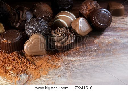 Fine chocolate pralines on cocoa powder as a love gift corner background with copy space on rustic wood selected focus narrow depth of field