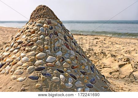 Sandy pyramid with many shells mosaic on a sea beach close-up