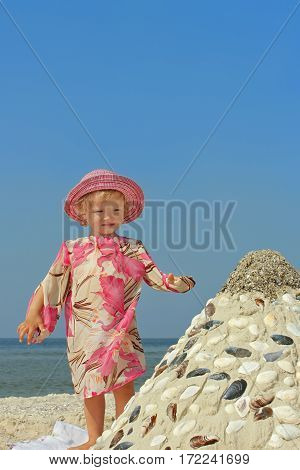 Beautiful little two-year girl standing on a sea beach near the sandy pyramid with shells on the background of a blue cloudless sky