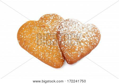 Two heart shaped gingerbread cookies with powdered sugar isolated on white background