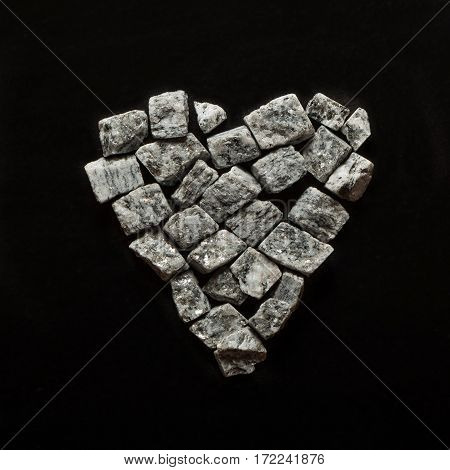 beautiful crushed granite gray on a black background, stone heart