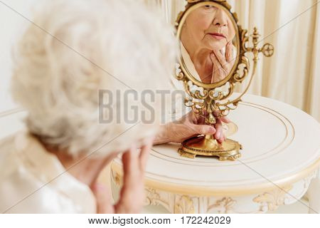 Pensive mature lady is sitting and looking at her wrinkles through mirror. She is touching face with sadness