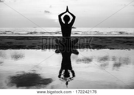 Yoga silhouette. Woman doing meditation near the ocean beach. Black and white photo.